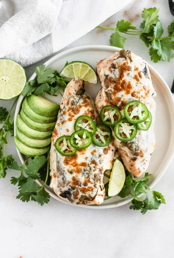 Grilled green chile chicken on a plate with avocado, jalapeños, cilantro, and lime.
