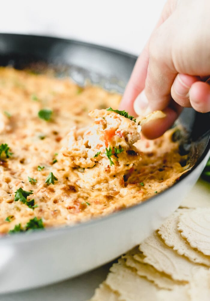 hand dipping a chip into a skillet of healthier hot crab dip.