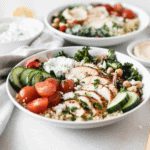 sliced greek chicken, tomatoes, cucumbers, kale, chickpeas and roasted onions with tzatziki sauce in a white bowl.