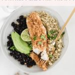 healthy tortilla crusted tilapia in a bowl with quinoa, black beans, and avocado.