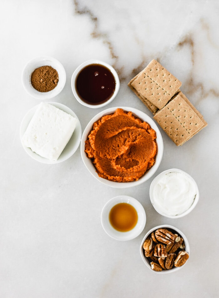 overhead view of ingredients needed to make healthy no bake pumpkin cheesecake on a white marble background.