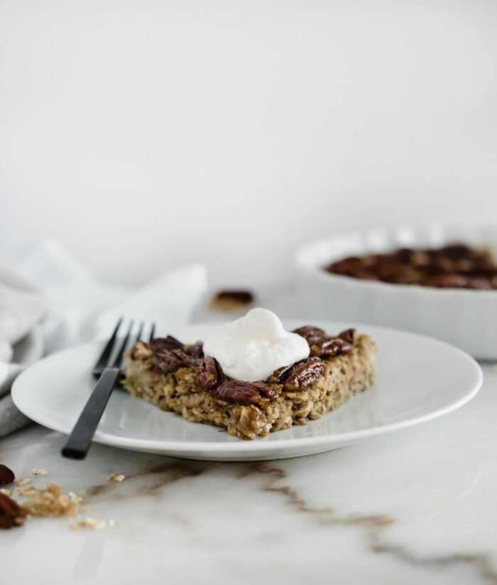 A slice of healthy pecan pie baked oatmeal with greek yogurt on top.