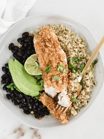 healthy tortilla crusted tilapia on a plate with quinoa, black beans, and avocado.