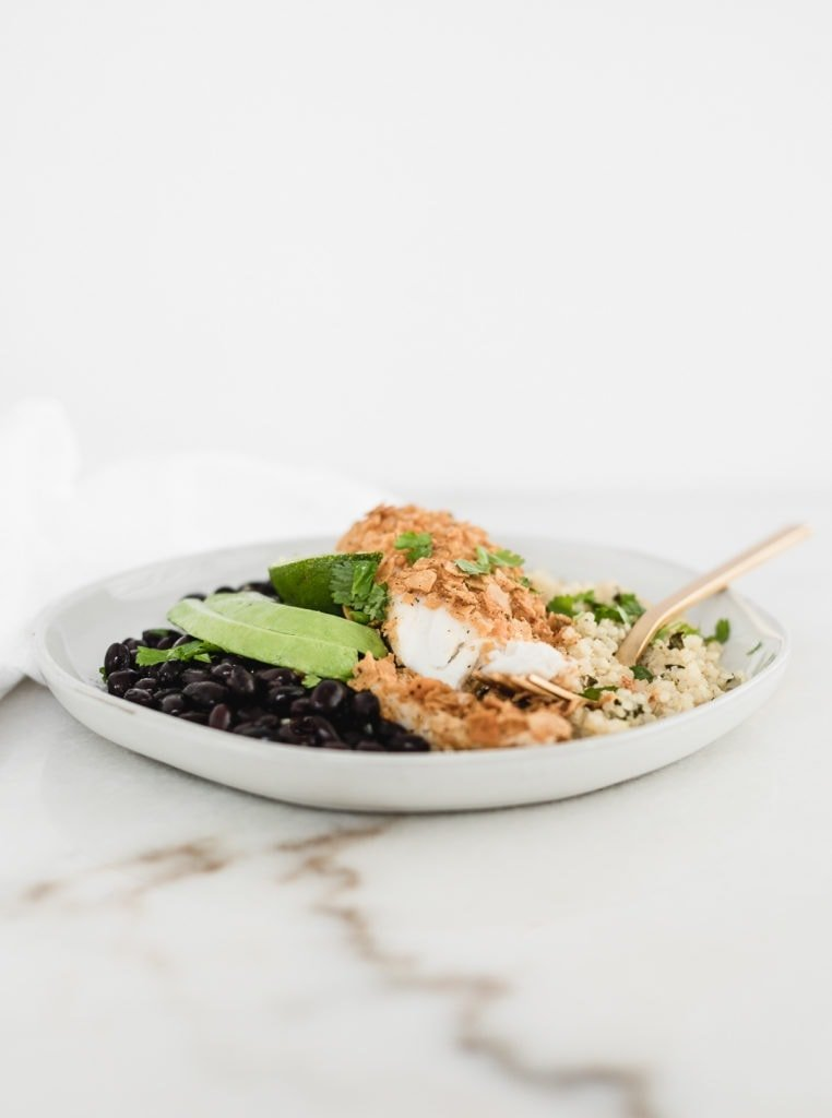 healthy tortilla crusted tilapia cut into on a plate with quinoa, black beans, and avocado.