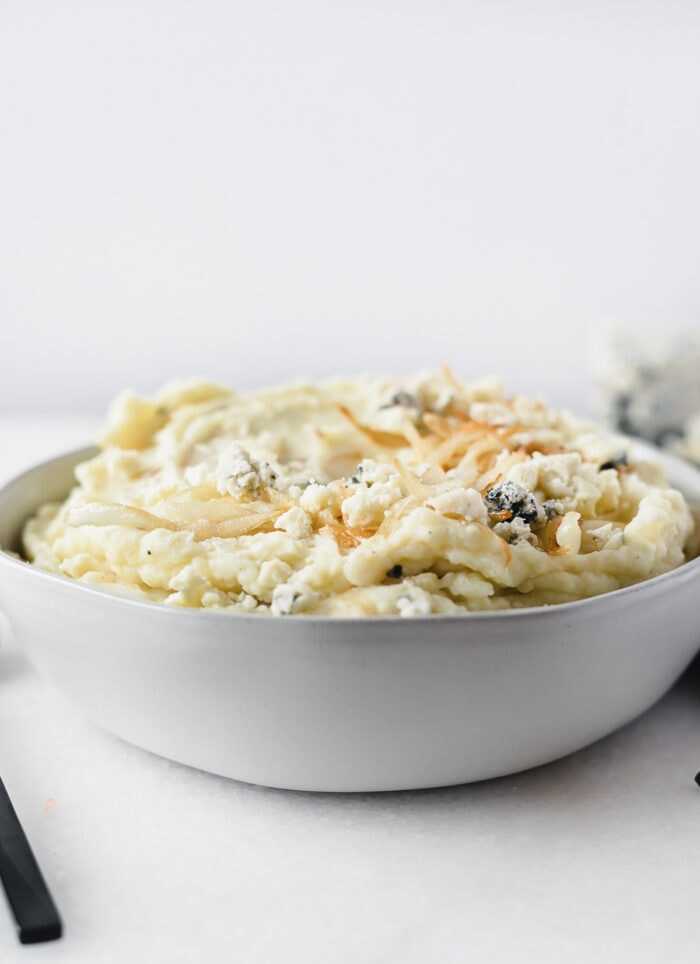 bowl of blue cheese mashed potatoes with caramelized onions and blue cheese crumbles on top.