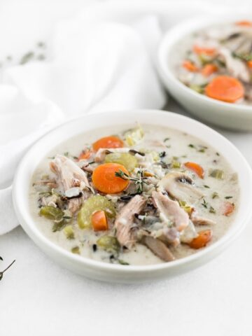 white bowl of healthy turkey and wild rice soup with another bowl of soup in the background.