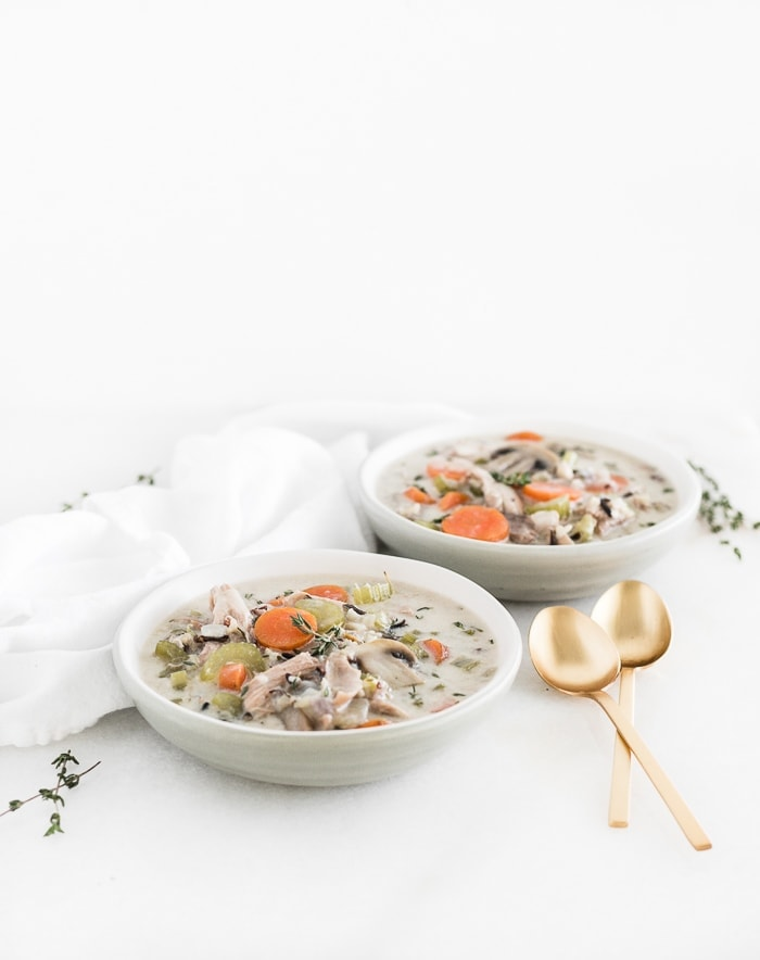 two grey bowls of turkey and wild rice soup with two gold spoons.