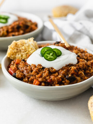 vegan pumpkin lentil chili in a small white bowl with cheese on top.