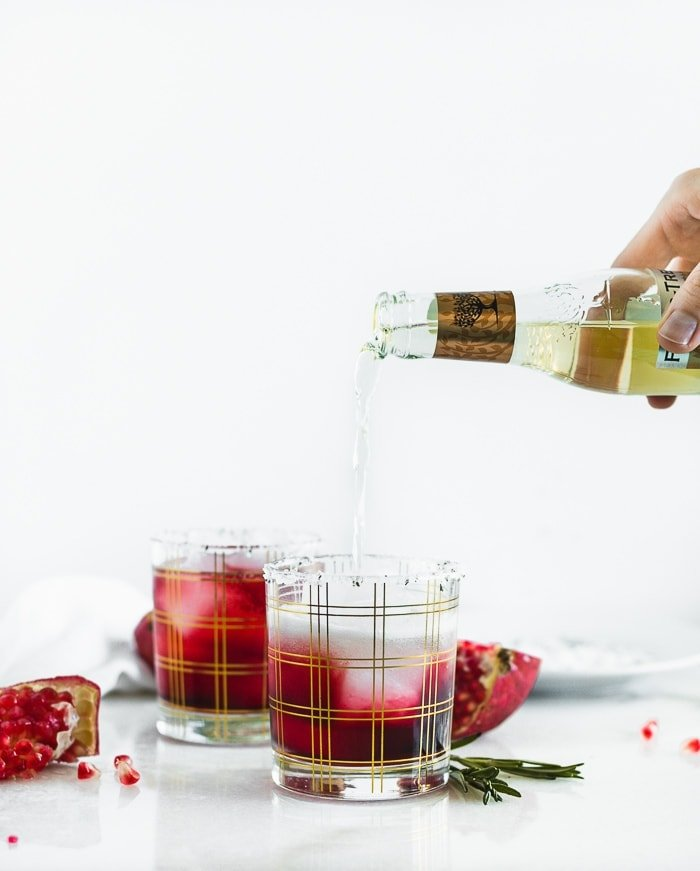 Hand pouring ginger beer into a glass of pomegranate juice.