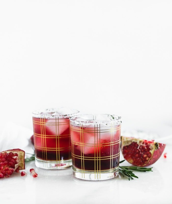 two pomegranate ginger smash cocktails in gold plaid cocktail glasses surrounded by pomegranate pieces and rosemary.