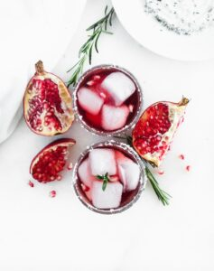 overhead view of two pomegranate ginger smash cocktails surrounded by rosemary and pomegranate pieces.