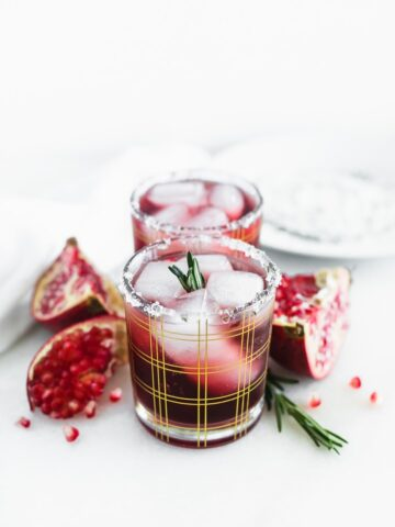 two pomegranate ginger smash cocktails in a straight line in gold plaid cocktail glasses surrounded by pomegranate pieces and rosemary.