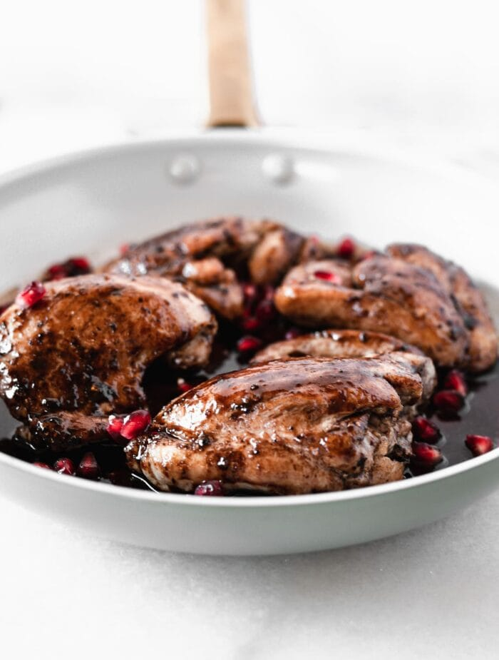 pomegranate balsamic chicken thighs in a skillet with balsamic sauce and pomegranate arils on top.