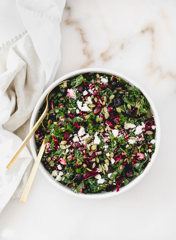 overhead view of shredded beet kale salad in a white bowl with gold spoons in it.
