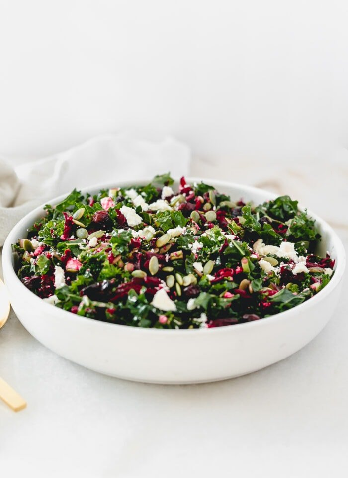 shredded beet kale salad in a white bowl.