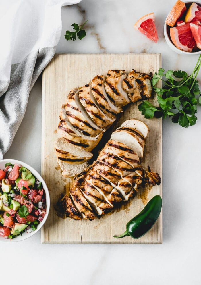 overhead view of sliced chicken breast on a cutting board with grapefruit jalapeno salsa, cilantro, and a jalapeno around it.