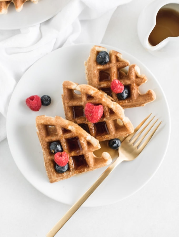 overhead view of three sourdough waffle triangles on a white plate topped with berries and syrup with a gold fork beside them.