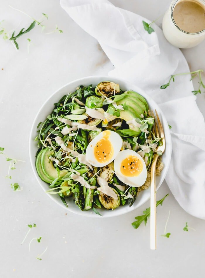 overhead view of spring green grain bowl with a soft boiled egg on top.