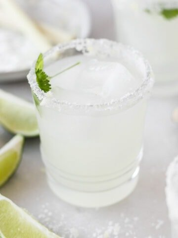 lemongrass margarita in a glass with cilantro and ice in it surrounded by lime slices and salt.