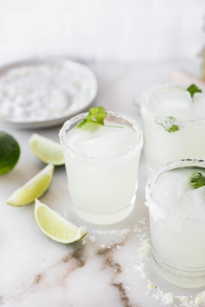 3 lemongrass margaritas in a glasses surrounded by limes and salt with a plate of salt in the background.