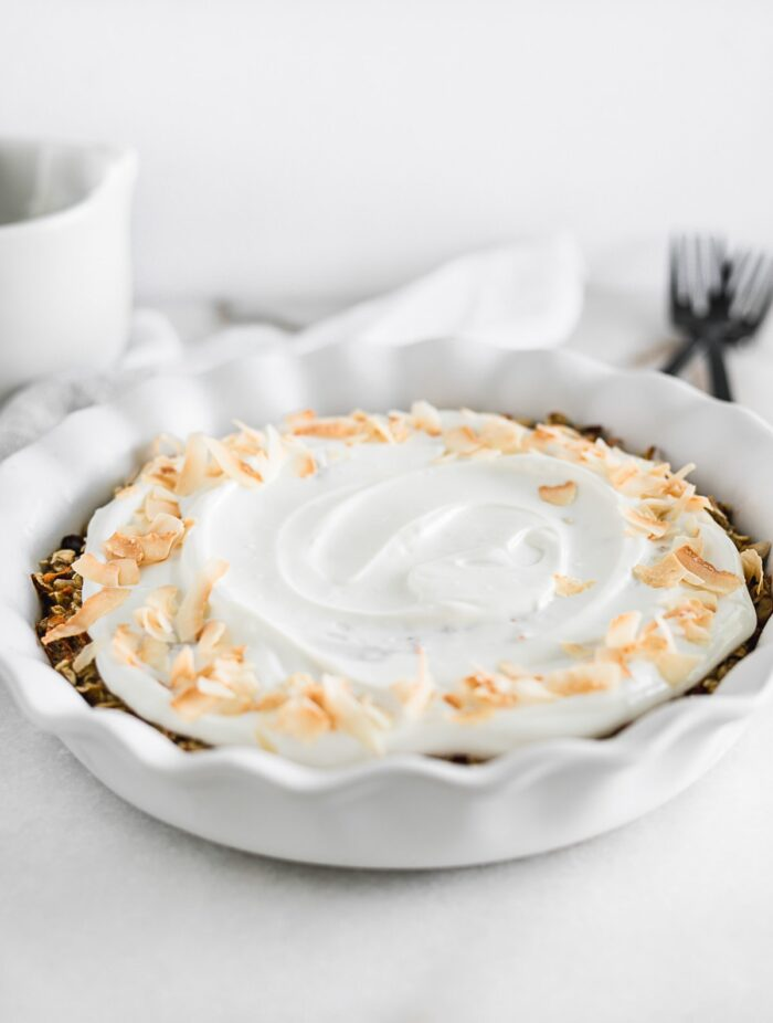 Healthy carrot cake baked oatmeal covered with glaze in a pie dish.