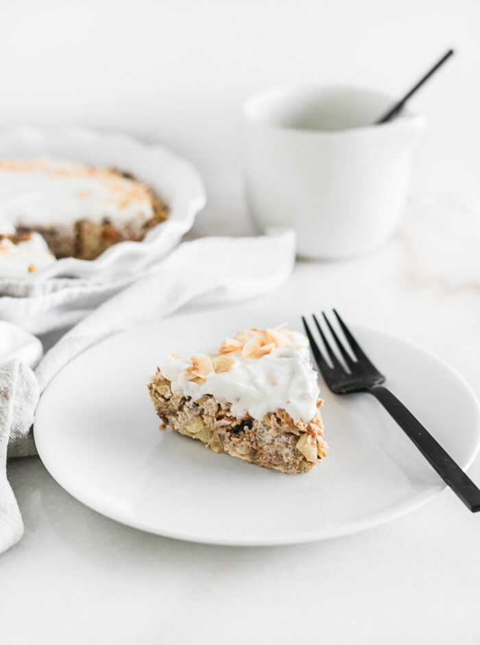 A slice of healthy carrot cake baked oatmeal on a plate with a fork.