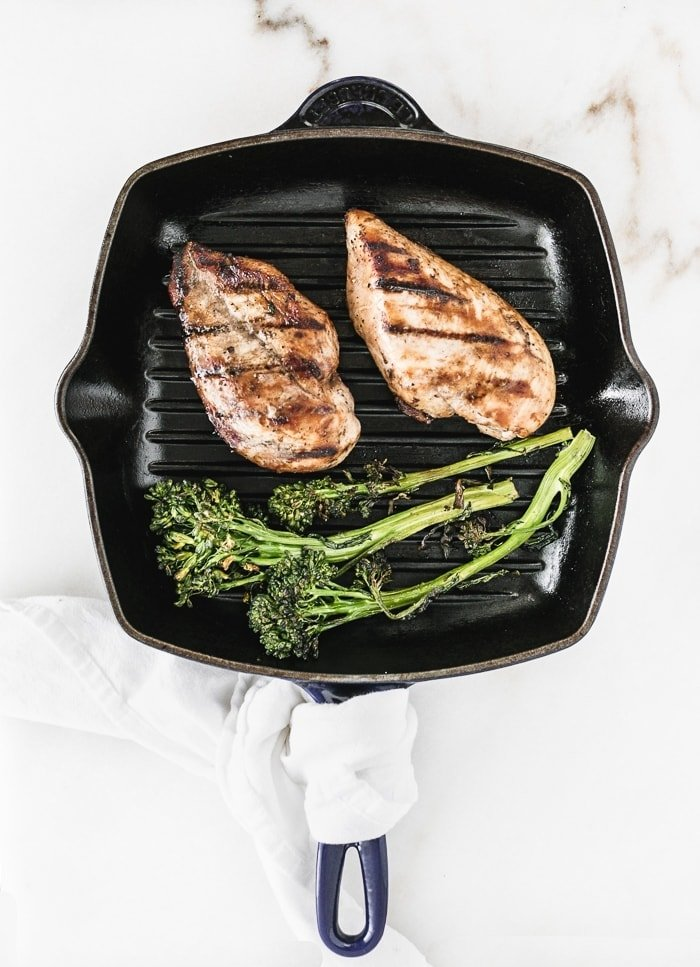 blue square grill pan with 2 grilled chicken breasts and grilled broccolini.