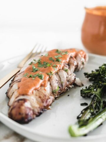 sliced grilled chicken breast with romesco sauce on top and sprinkled with parsley on a grey plate with broccolini.