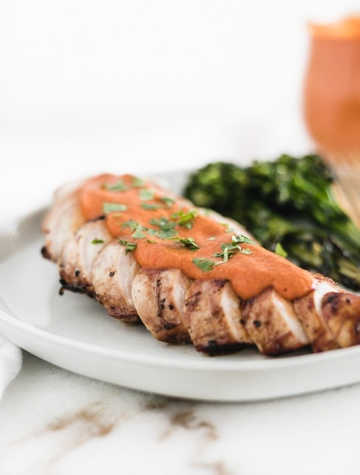 grilled sliced chicken breast topped with romesco sauce and sprinkled with parsley.