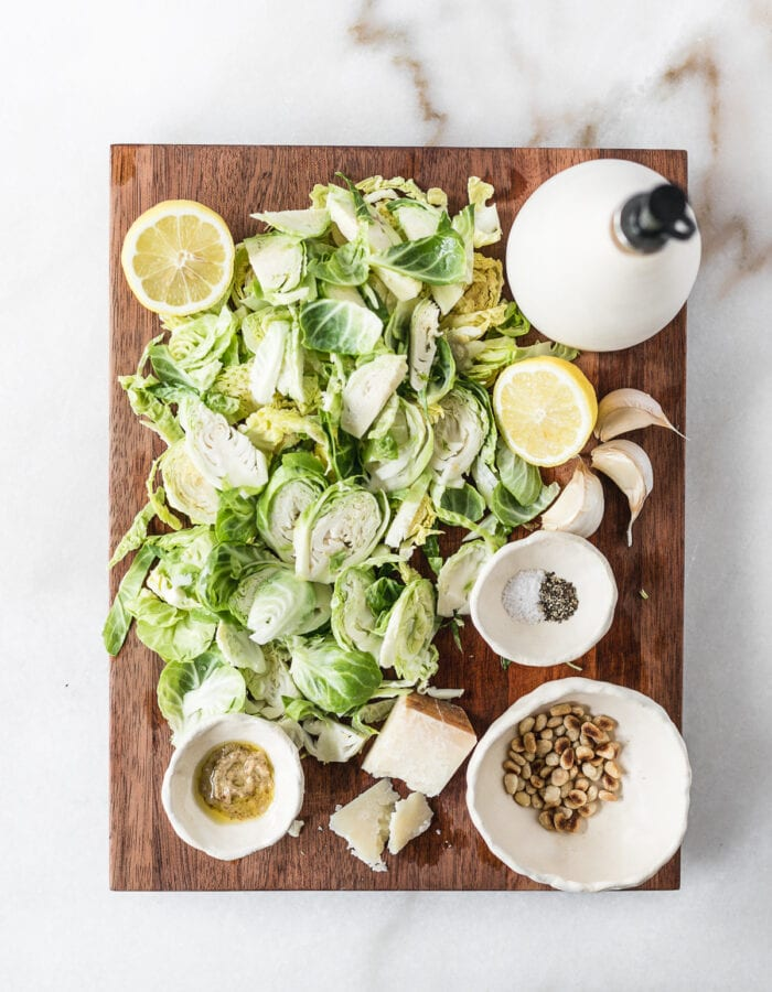 overhead view of ingredients needed to make lemon parmesan shaved brussels sprouts on a wooden cutting board.