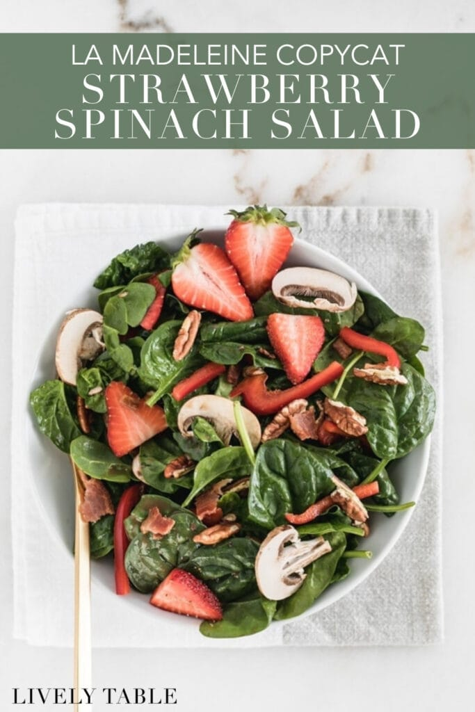 overhead view of strawberry spinach salad in a white bowl with text overlay.