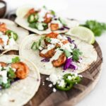 shrimp taco on a wooden cutting board with jalapeno lime cream sauce, cotija, purple cabbage and cilantro.