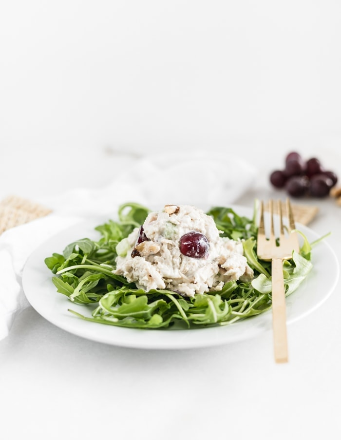 scoop of greek yogurt chicken salad on top of a bed of lettuce on a white plate.