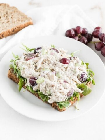 greek yogurt chicken salad with grapes on top of a piece of bread on a white plate.