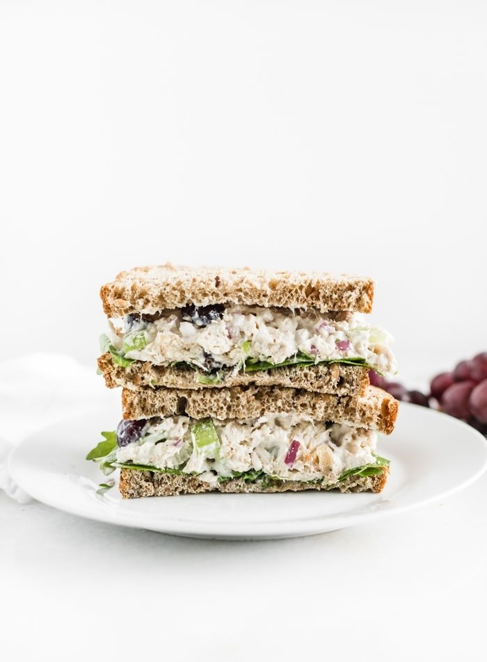 healthy greek yogurt chicken salad sandwich halves stacked on top of each other on a white plate.