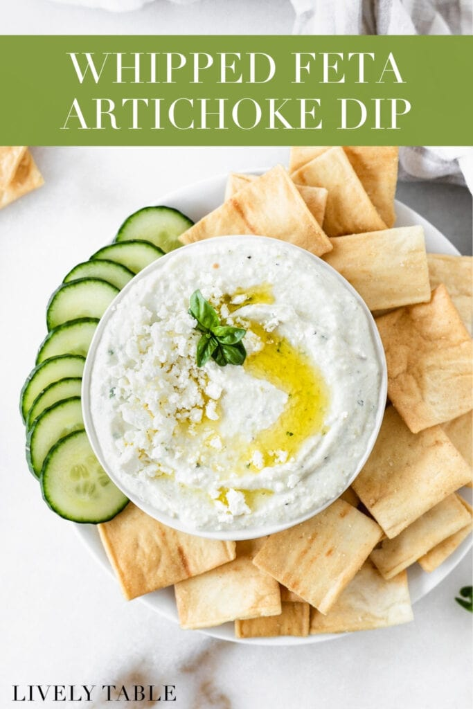 overhead view of whipped feta artichoke dip in a bowl surrounded by pita chips and sliced cucumbers with text overlay.