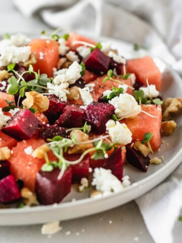 closeup of watermelon beet salad with goat cheese and walnuts in a grey plate.