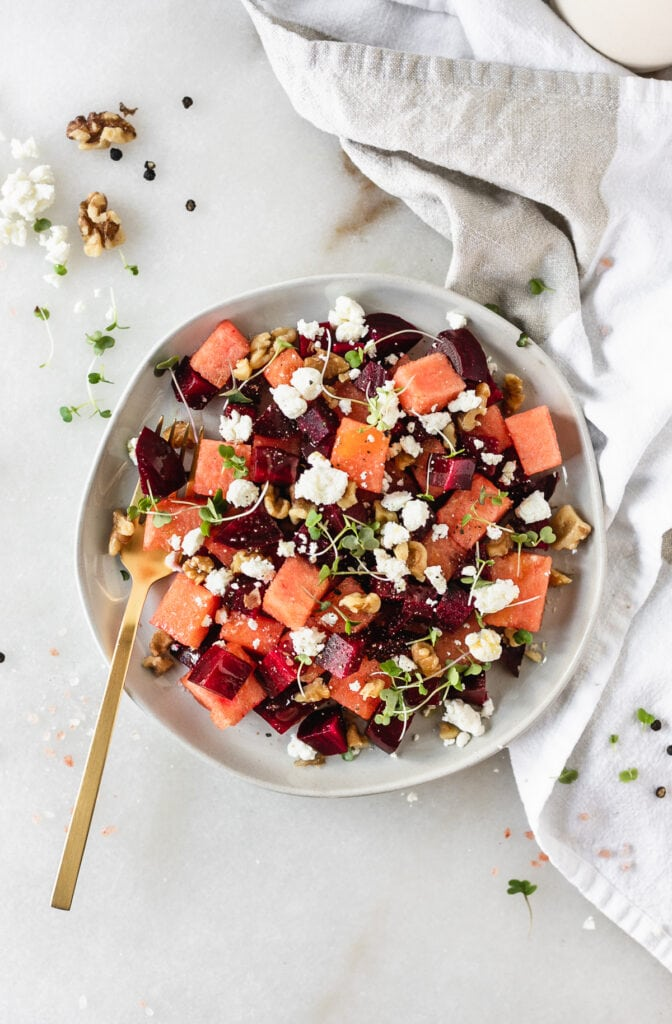 overhead view of watermelon beet salad on a grey plate with a gold fork in it.