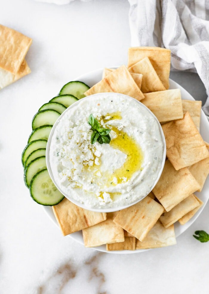 overhead view of whipped feta artichoke dip in a bowl surrounded by pita chips and sliced cucumbers.