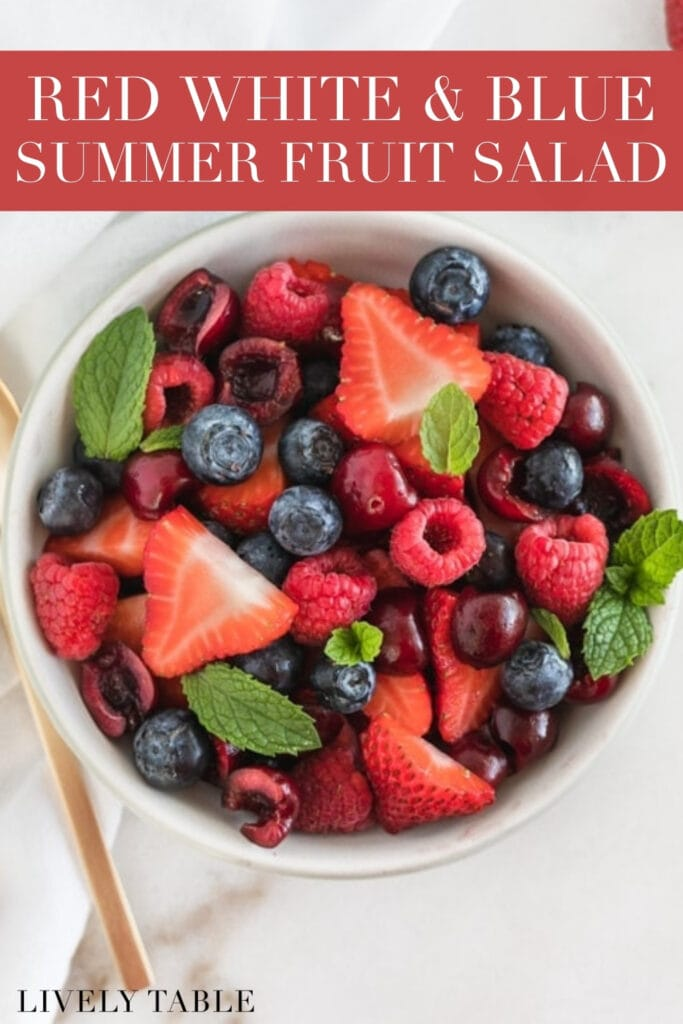 red white and blue summer fruit salad in a grey bowl with text overlay.