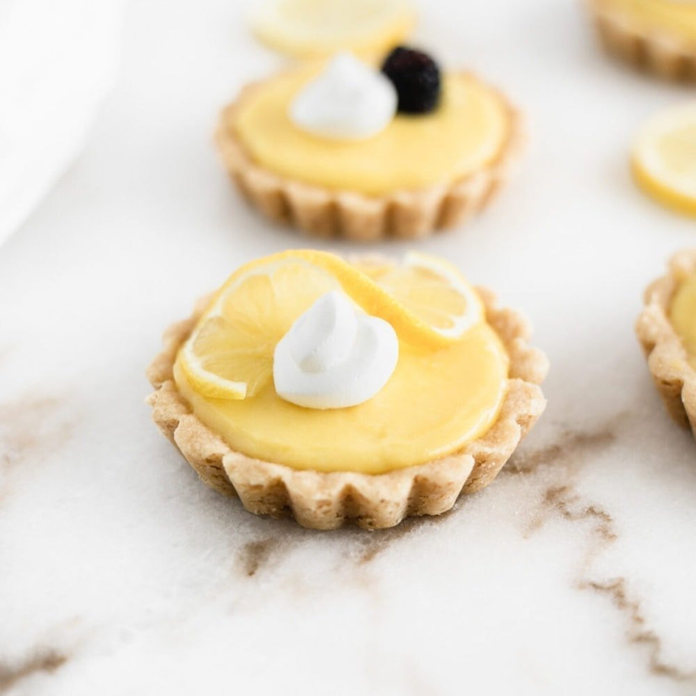 mini lemon tart with shortbread crust with whipped cream and a lemon slice on top, with lemon tarts in the background.
