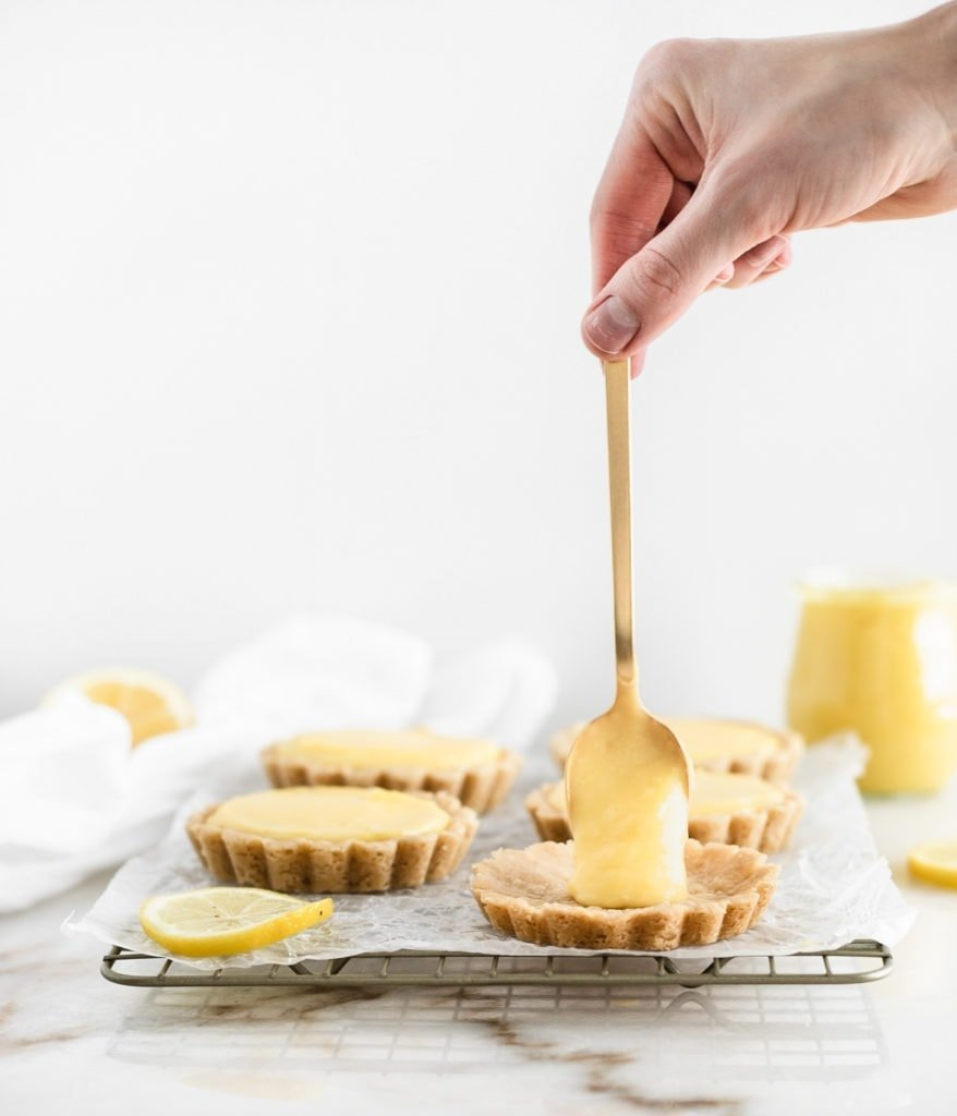 hand using a gold spoon to spoon lemon curd onto mini tart crust.