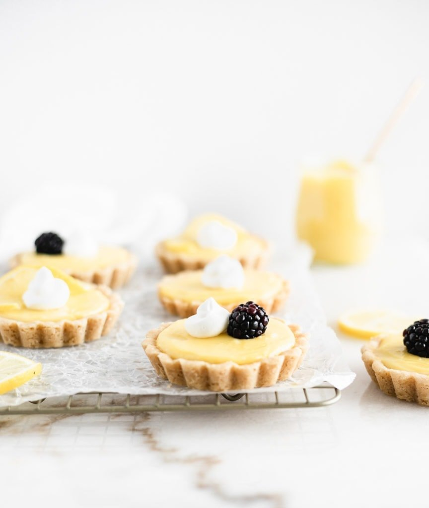 mini lemon tarts topped with whipped cream, berries, and lemon slices on a cooling rack.