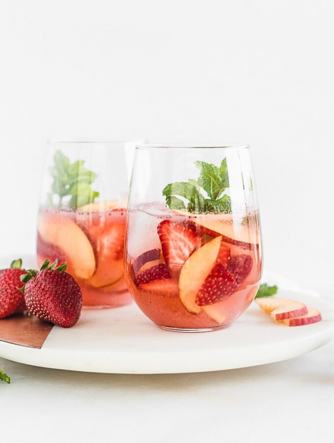 two glasses of rose sangria with peaches and strawberries on a round white marble board.
