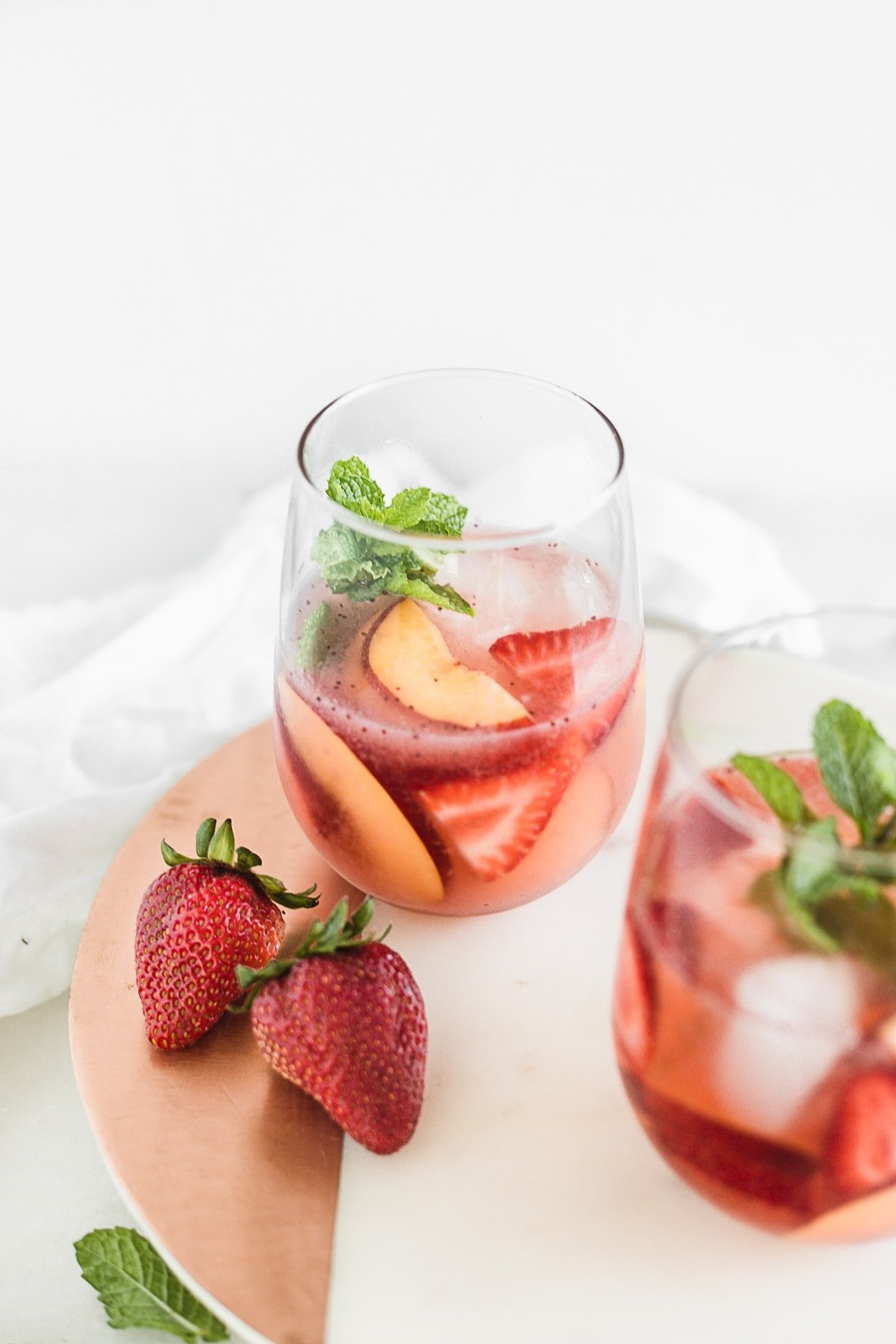 This fruity rosé sangria made with strawberries, peaches and raspberry puree is an easy and delicious summer party drink to serve at backyard BBQs and to sip by the pool! | via livelytable.com