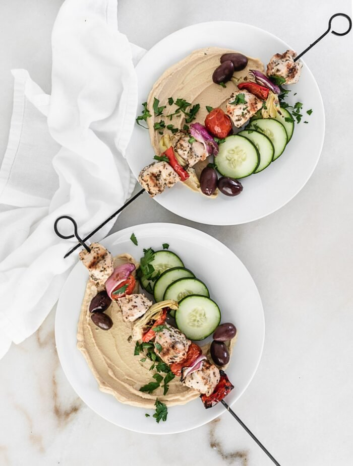Two bowls with Mediterranean chicken kebabs with hummus, cucumbers, and olives.