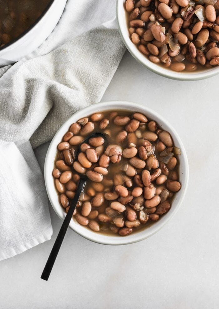overhead view of pinto beans in a grey bowl with a black spoon in it.