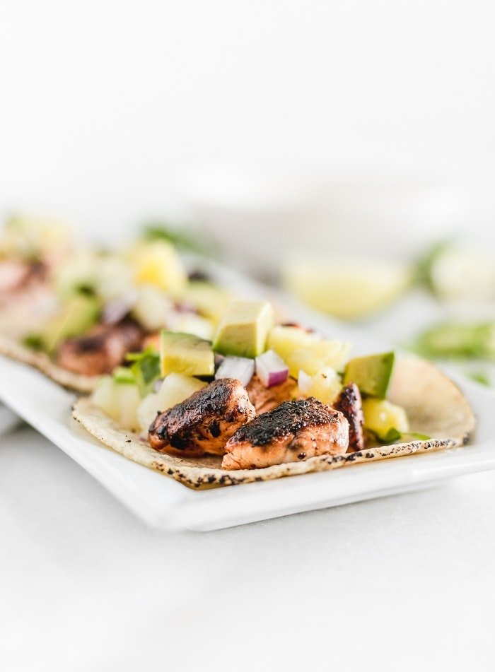 Close up of three blackened salmon tacos with pineapple salsa on a plate.