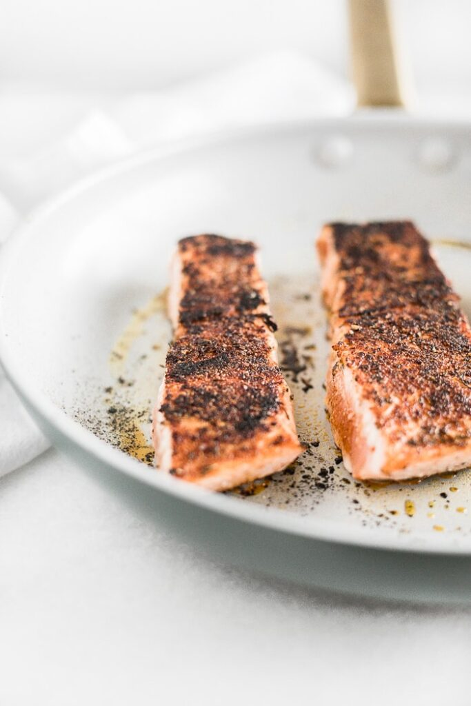 Blackened salmon getting cooked in a pan.