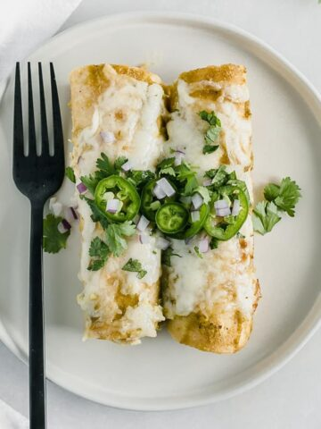 overhead view of two green chile chicken enchiladas on a white plate topped with jalapeno slices and cilantro with a black fork beside them.